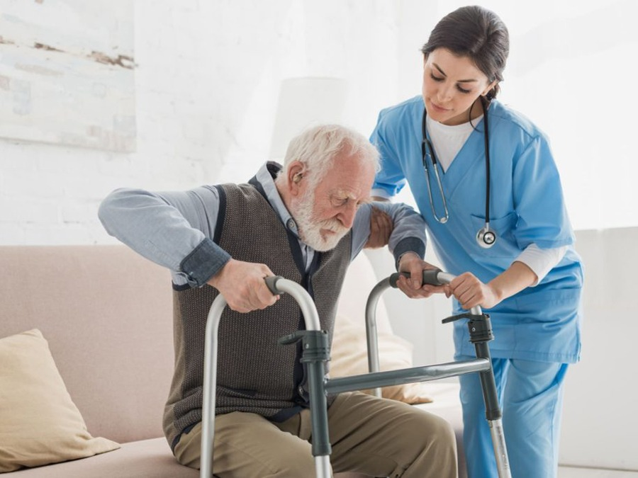 Aid helping older man stand up to use walker