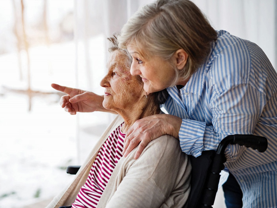 Woman pointing out window to show an elderly woman something