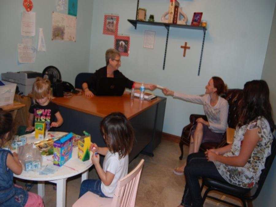 women talking while children color at table