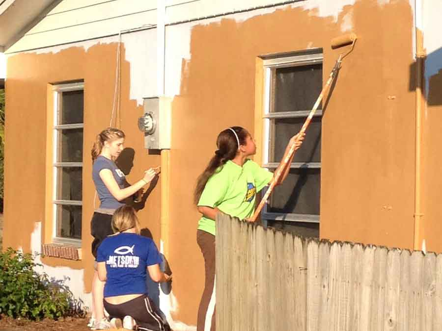Girls painting exterior building wall