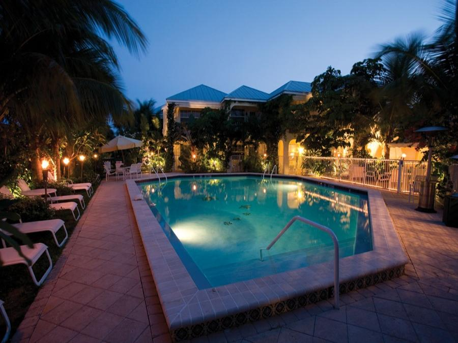 The Caribbean Court Boutique Hotel pool with lounge chairs and tropical landscaping