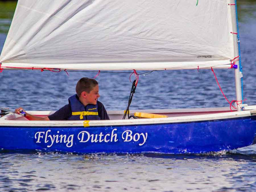 Young boy sailing his boat 'Flying Dutch Boy'