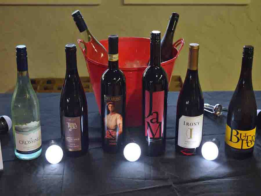 Photo display of six wine bottles on table and two in a red bucket