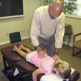 Dr. Parris adjusting young girl's back