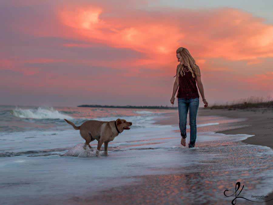 woman walking beach with dog