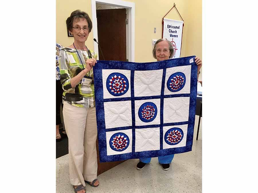 President Helen Marner and friend holding up quilt