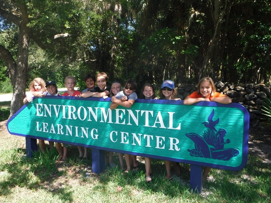 Children standing behind the Environmental Learning Center sign