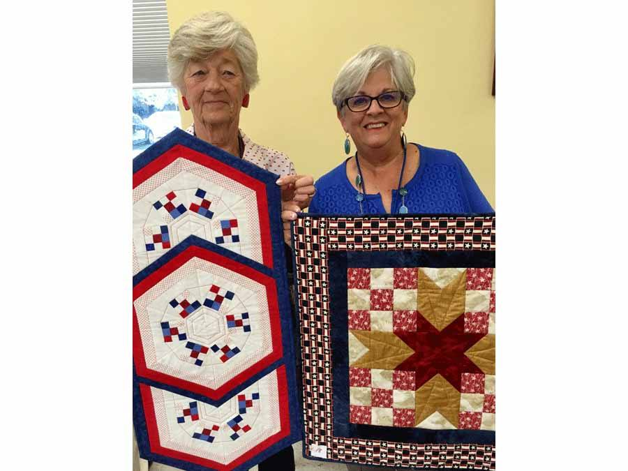 Diane Larrabee and Linda Jackson showing items they made