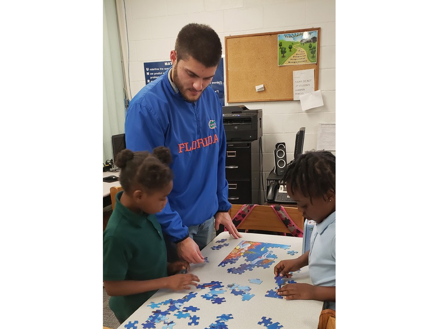 GYAC 1st grade teacher assisting students with a puzzle
