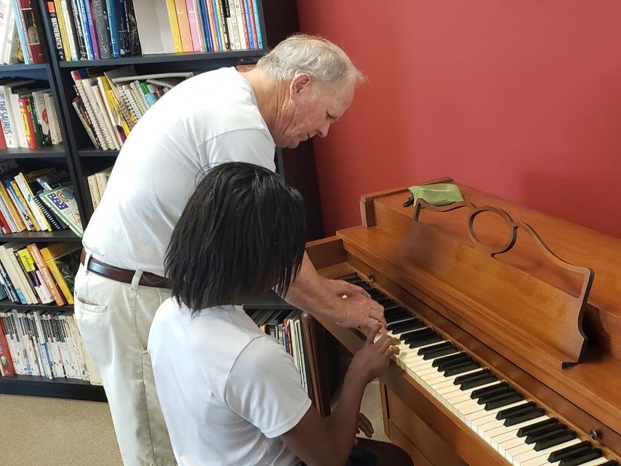 GYAC volunteer playing the piano with a student