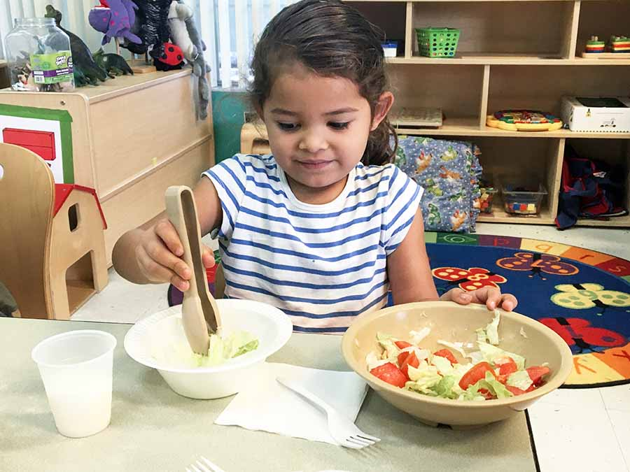 Young girl getting bowl of salad