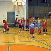 Young kids playing basketball in gymnasium