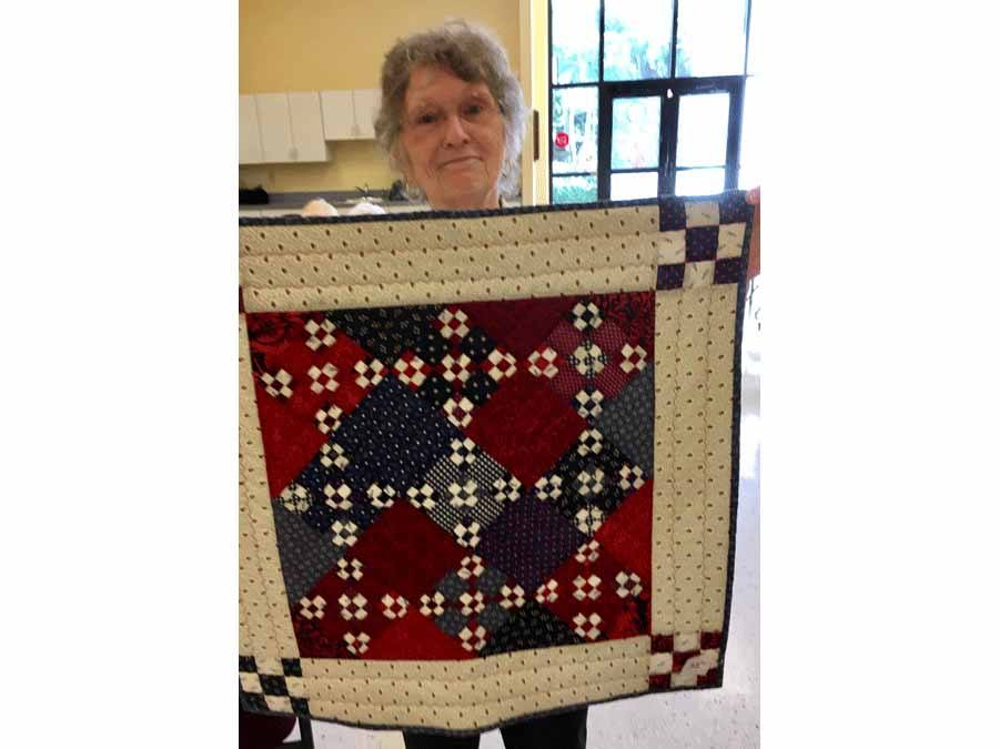 Marcia Haberman holding up quilt she made