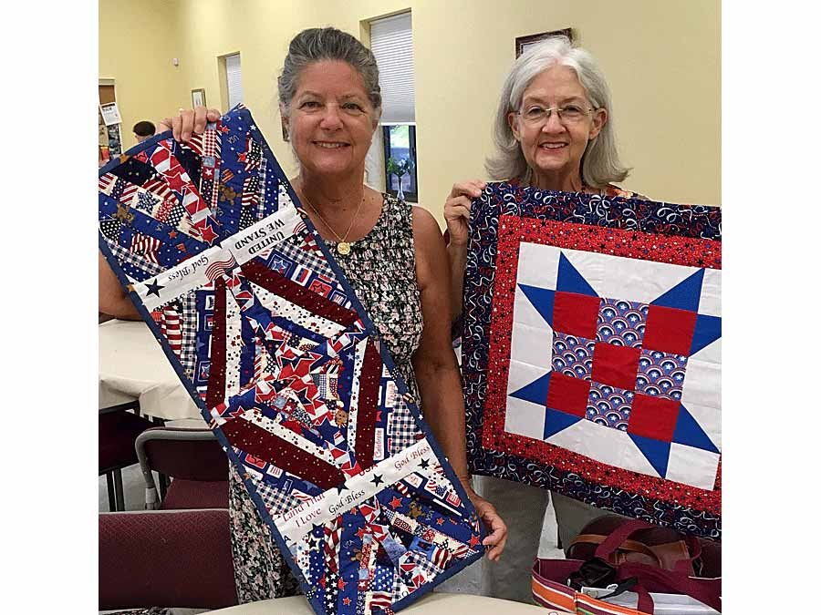 Millie Bernier and Ann Montgomery holding up items made at guild