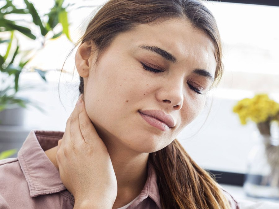 Woman rubbing neck because of pain