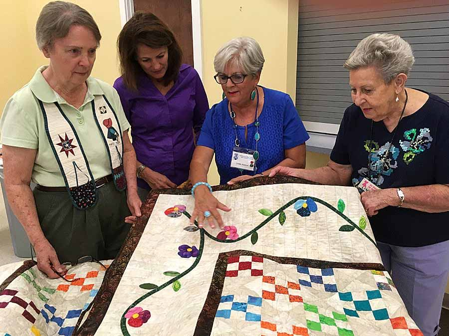 four women admiring the details on a quilt