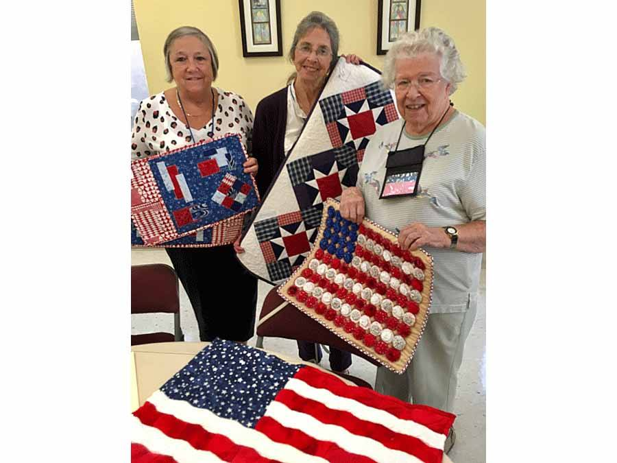 three women displaying their quilts