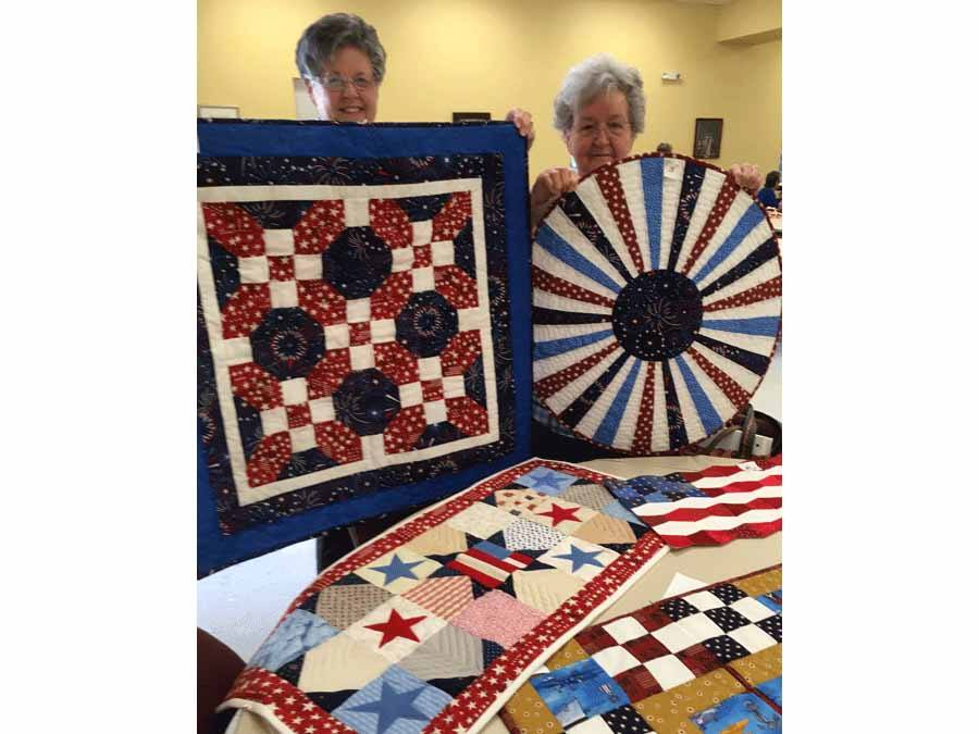 Roberta McCullough and Judy White displaying some of the quilts made at the guild