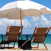 two beach chairs and umbrella on beach