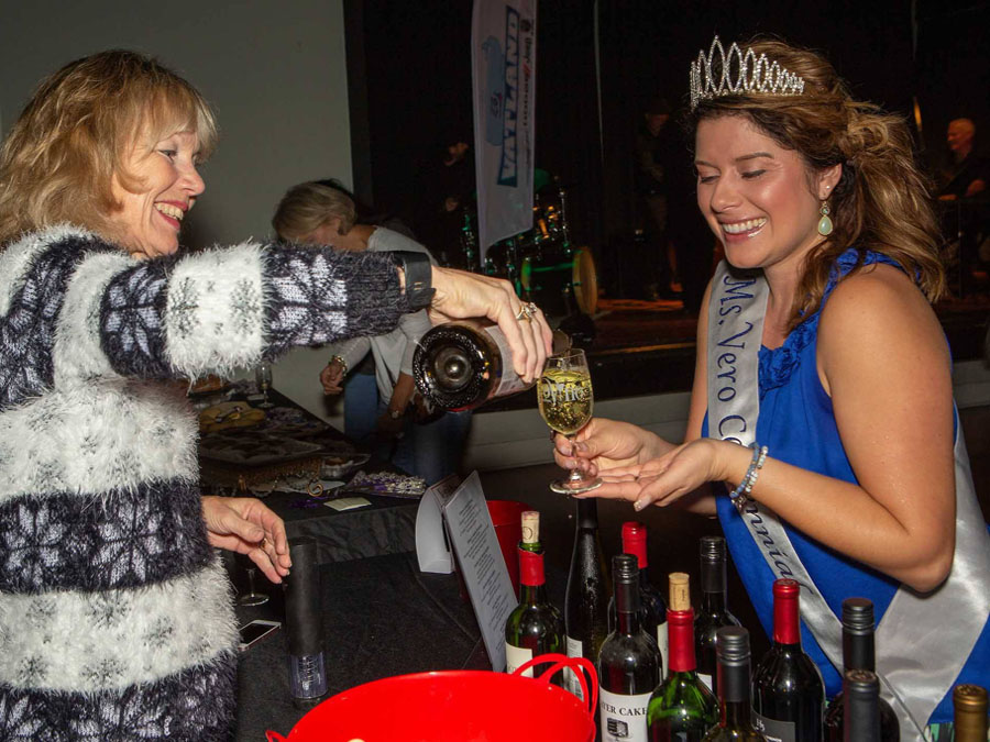 Lady pouring white wine in a glass for Miss Centennial