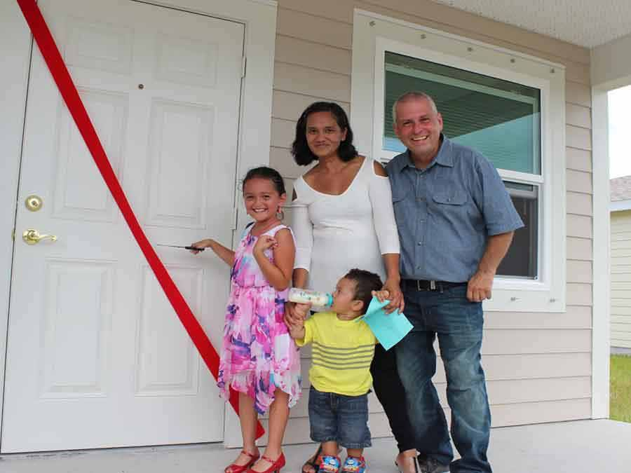 Family standing at front door of their new home
