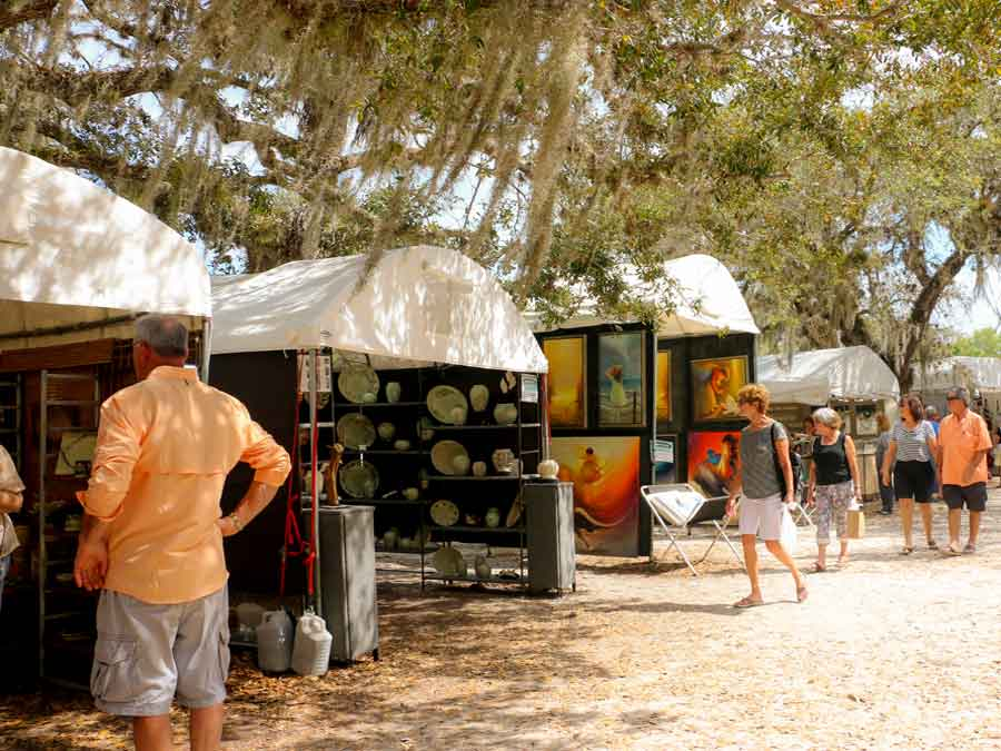 People looking at artwork in tents at the Under the Oaks Art Festival Vero Beach Florida