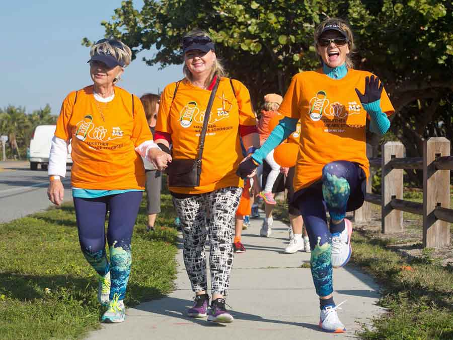 Three women participating in the walk, walking down the sidewalk