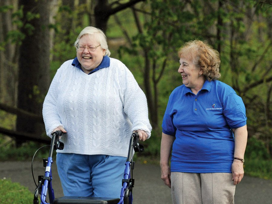 two women taking a walk. One has a walker