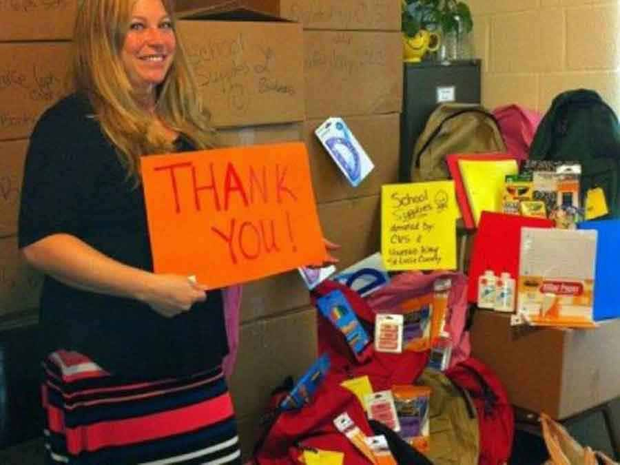 HoGirl holding a 'Thank you' sign in front of donations