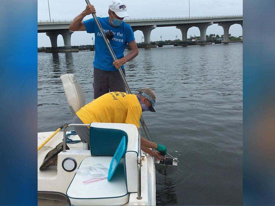 Men in boat reaching into water with monitoring equipment for ORCA in Vero Beach
