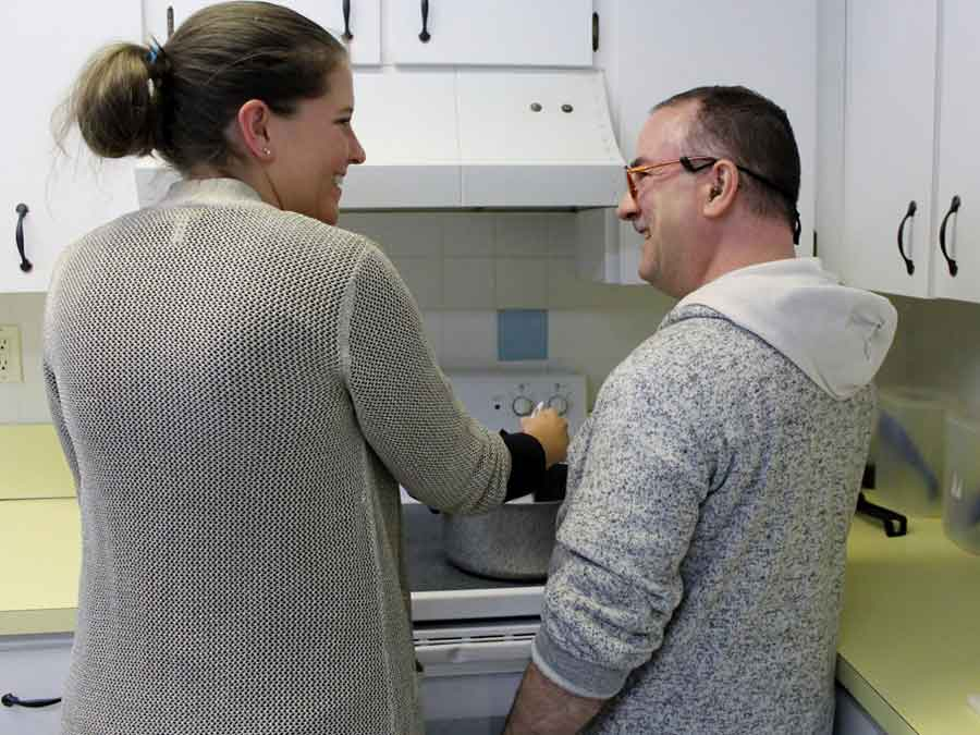 Woman teaching man cooking skills at home