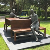 Sculpture of man and woman holding hands while sitting across from each other at a picnic tableat Vero Beach Museum of Art Vero Beach Florida