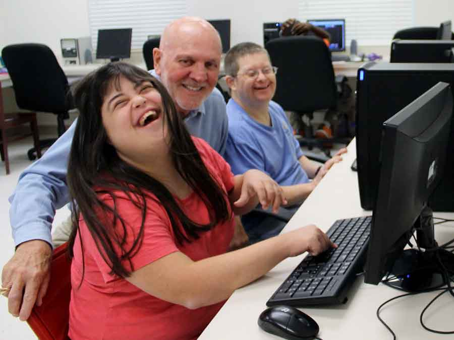 Woman laughing while learning to use the computer