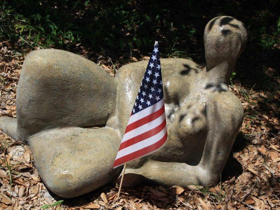 sculpture with humane form outside with American flag next to it