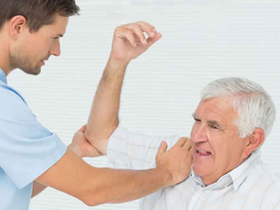 Male therapist stretching man's shoulder