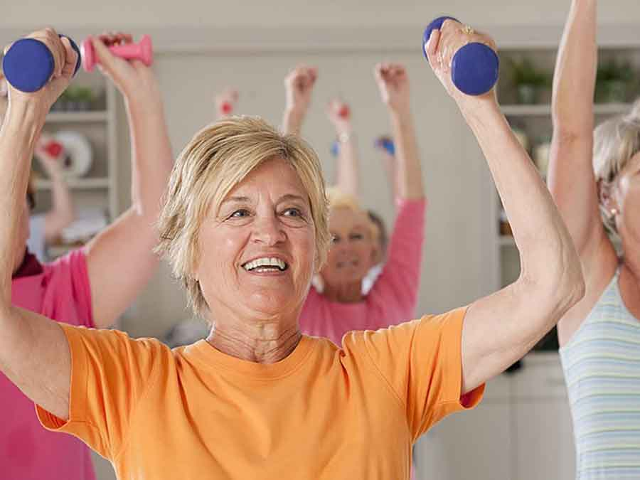 women holding dumb bells while doing exercises in class